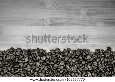A pile of coffee beans forming a simple stripe frame on a natural background,  black and white photo - stock photo