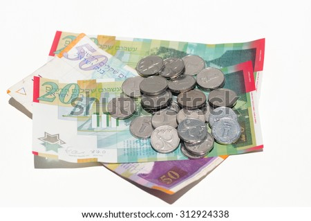 A pile of coins and banknotes of New Israeli Shekels (NIS) on white background - stock photo