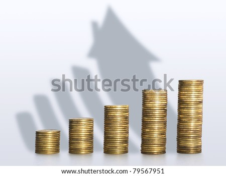 A pile of coins casting a shadow as house, savings concept - stock photo