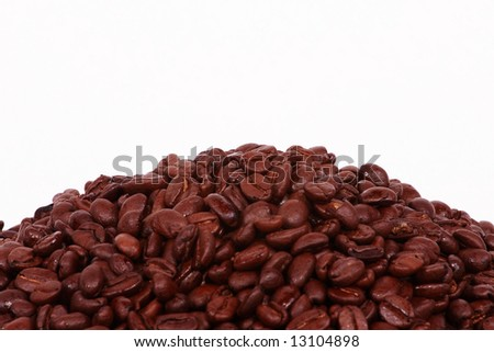 A pile of Colombian Coffee beans on the lower third of a white background. - stock photo