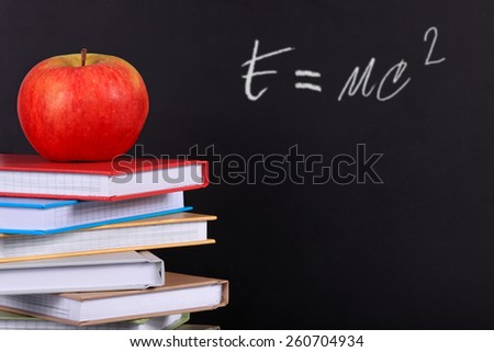 A pile of colored books on a desk with a red apple and copy space on a blackboard. - stock photo