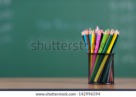 A pile of colored pencils in a black metal holder inside the classroom - stock photo