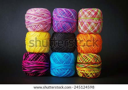 A pile of colorful yarn coils over grey background  - stock photo