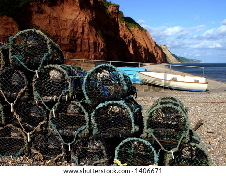 A pile of crab baskets fronts the view of the beach and triassic era mudstone cliffs at Sidmouth, Devon, England - stock photo