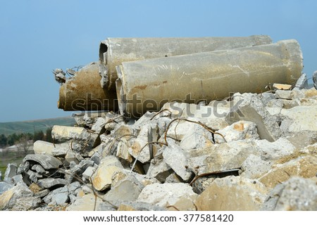 A pile of debris topped by old concrete sewer pipe results from a contractor's demolition of a building. - stock photo