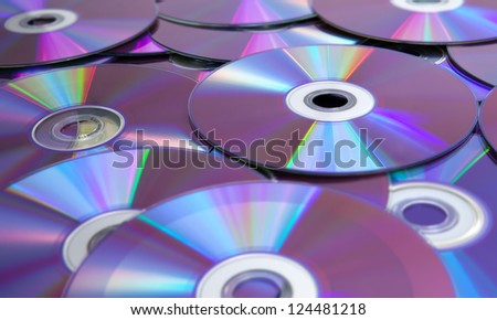 A pile of DVDs showing their bottom sides. - stock photo
