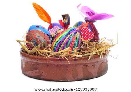a pile of easter eggs painted in different colors and patterns in a earthenware bowl with straw, on a white background