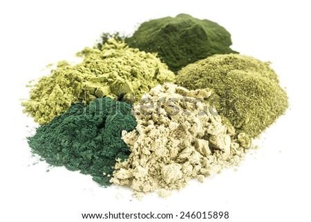a pile of five healthy green dietary supplement powders (spirulina, chlorella, wheatgrass, kelp and moringa leaf) - stock photo