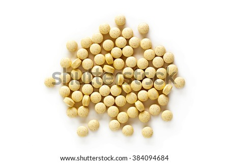A pile of folic acid vitamin supplement tablets isolated on a white background from above.