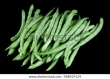 A pile of French Beans isolated against a black background