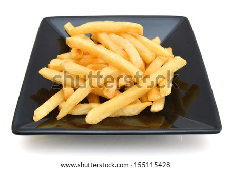 a pile of french fries isolated in black plate on white  - stock photo