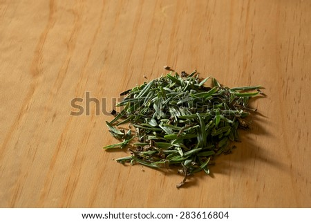 A pile of fresh cut lavender leaves on wooden surface lit by window light. - stock photo