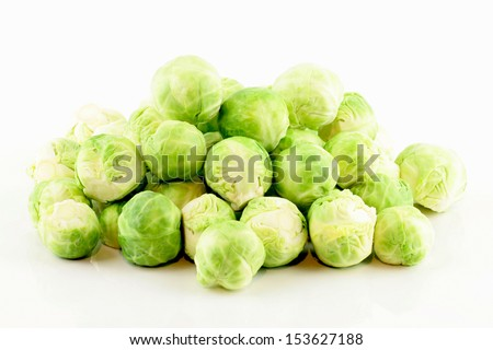 A pile of fresh green brussels sprouts (Brassica oleracea). On a white background. - stock photo