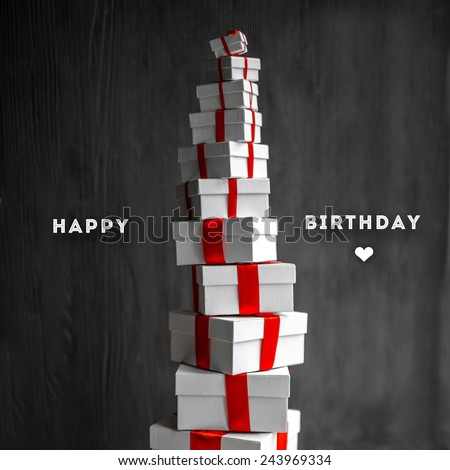 A pile of gift boxes with red ribbons on wooden background with greeting text. Greeting card concept - stock photo