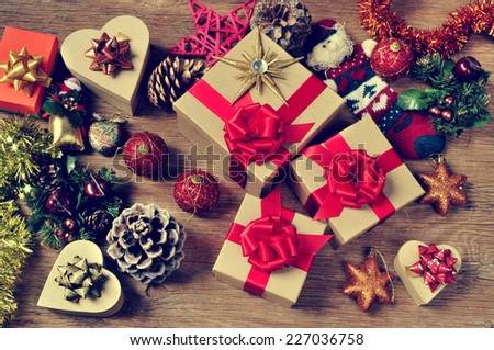 a pile of gifts and christmas ornaments, such as christmas balls, stars and tinsel, on a rustic wooden table - stock photo