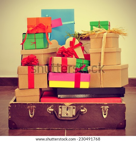 a pile of gifts of different colors and sizes in an old suitcase, with a retro effect - stock photo