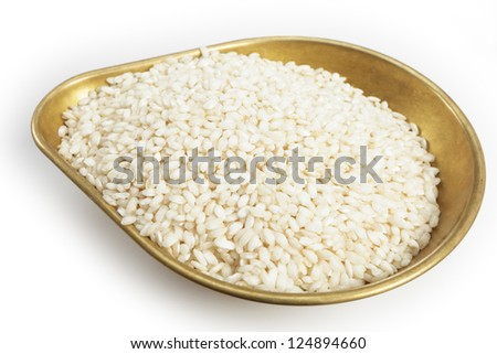 A pile of 460grams (one pound) of arborio Italian rice in the weighing pan from a set of scales, with a light shadow over white. - stock photo