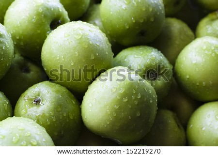 A pile of green apples for sale at a market