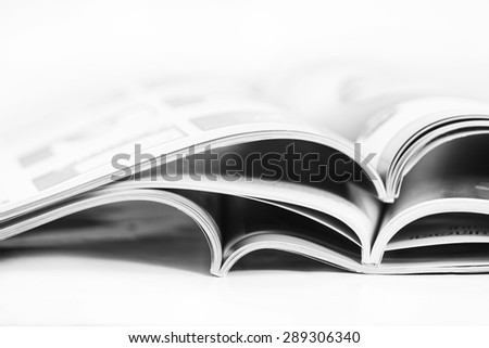 a pile of magazines close up on white background - stock photo