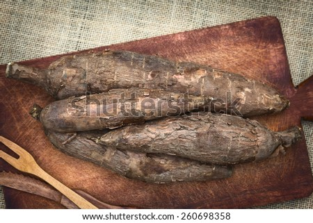 A pile of manioc (Lat. Manihot esculenta) on wooden board photographed with natural light (Selective Focus, Focus on the two upper maniocs) - stock photo