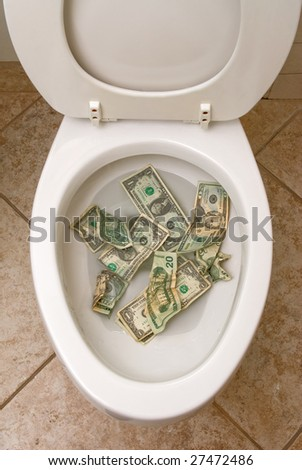 A pile of money getting ready to be flushed down the toilet. - stock photo