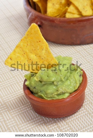 a pile of nachos and guacamole served in a restaurant - stock photo