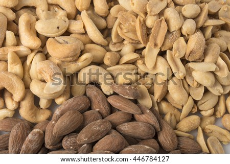 A pile of nuts including almonds, cashews, and peanuts.