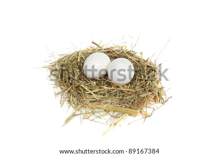 A pile of oat and two white egg on top as nest isolated on a white background