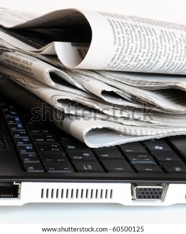 a pile of old newspapers on the notebook - stock photo