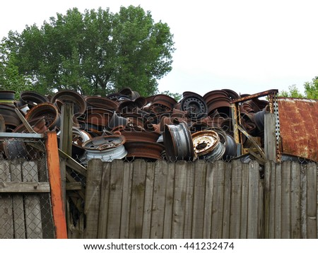 A pile of old rims in a junk yard - stock photo