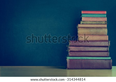 A pile of old, shabby, well used text books stacked in a pile on a light wood laminate desk in front of a black chalkboard.  Copy space on left side  Cross processed for retro or vintage effect. - stock photo