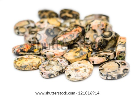 A pile of oval and colorful jasper beads with holes drilled through them. Nice patterns on these beads. - stock photo