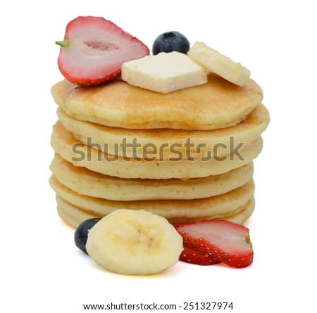 a pile of pancakes with fresh fruits isolated on white - stock photo