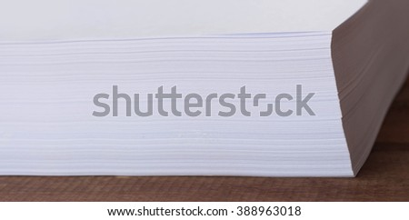 A pile of papers on a wooden table