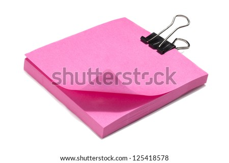 A pile of pink sticky note paper with a clip lying on a white background - stock photo