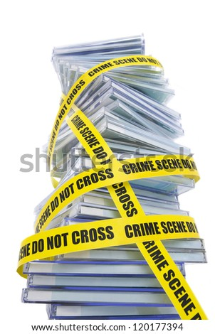 A pile of pirated compact disks warped in police tape - stock photo