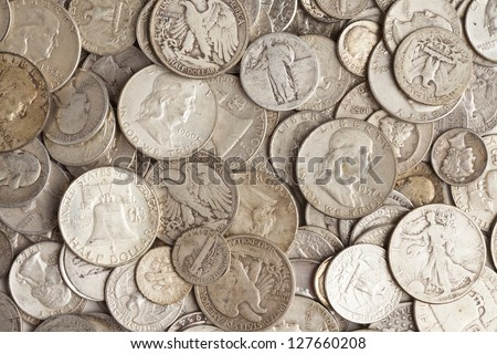 A pile of pure silver coins from different decades. - stock photo