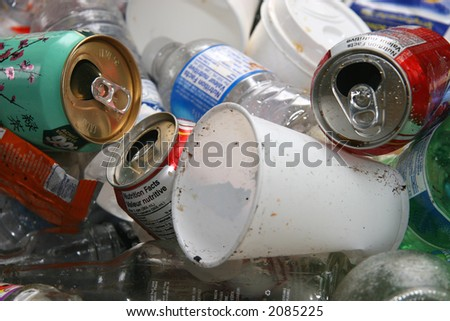 A pile of recyclable cans, cups and bottles in a recycle bin ready to be sorted and crushed. - stock photo