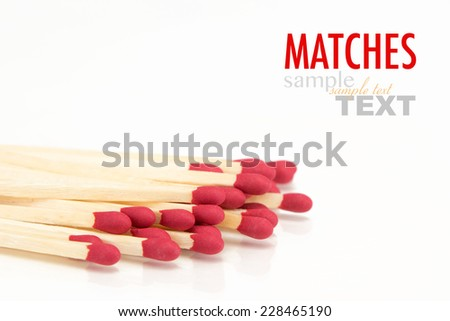 A pile of red match sticks with sample text. Close up shot in studio and isolated on a white background. - stock photo