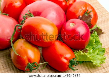 A pile of ripe red tomatoes and lettuce