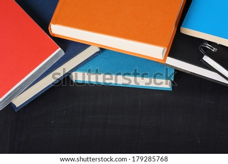A pile of school textbooks or hardback books on a blackboard with copy space for your text - stock photo