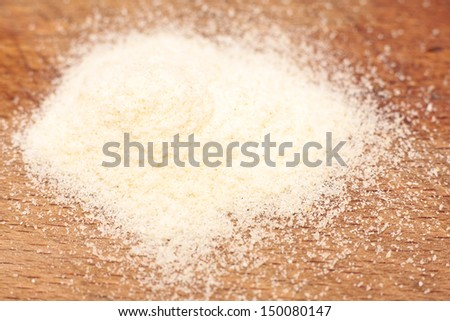 A pile of semolina flour on a wooden board