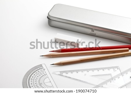 A pile of sharpened pencils with a white eraser, ruler, and protractor. - stock photo