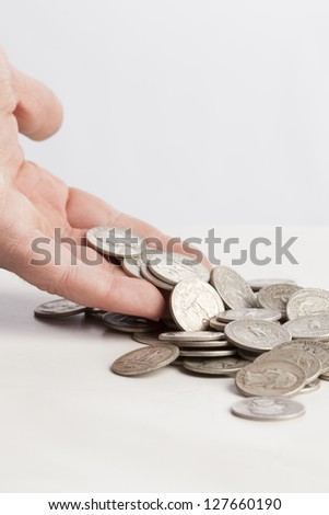 A pile of shiny silver coins is dropping from a hand on a table. - stock photo