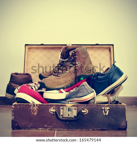 a pile of shoes in an old brown suitcase with a retro effect - stock photo