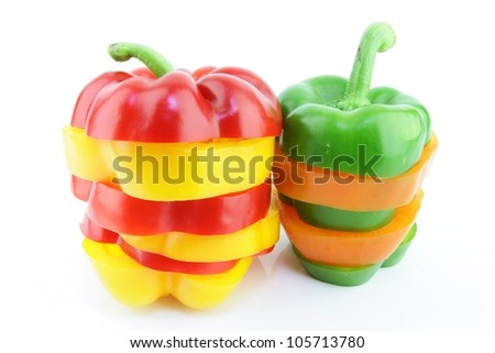 A pile of sliced red, yellow, orange and green paprika (Capsicum annuum) on a white background.