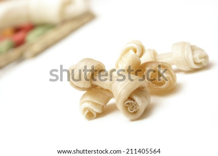 A pile of small rawhide bones infront of a bunch of other treats. - stock photo
