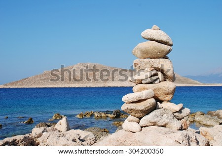 A pile of stones on Ftenagia beach at Emborio on the Greek island of Halki. The uninhabited island of Nissos is in the background. - stock photo