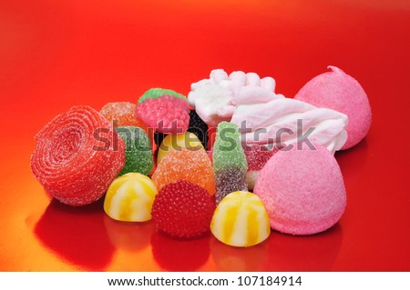 a pile of tasty candies on a red background - stock photo