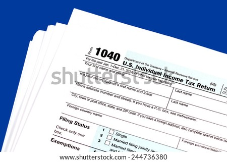 A pile of 1040 Tax Return Form on the blue background - stock photo